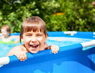 little boy playing in a swimming pool in summer