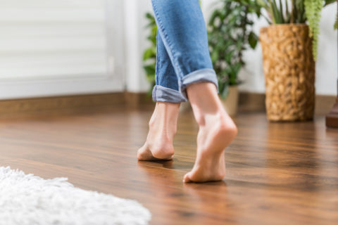 Person walking barefoot on hardwood floor
