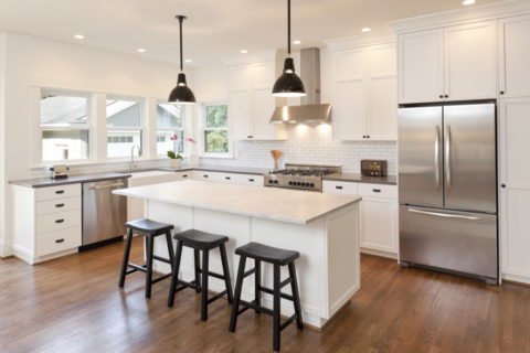 Newly renovated kitchen with white cabinets and countertops and stainless steel appliances