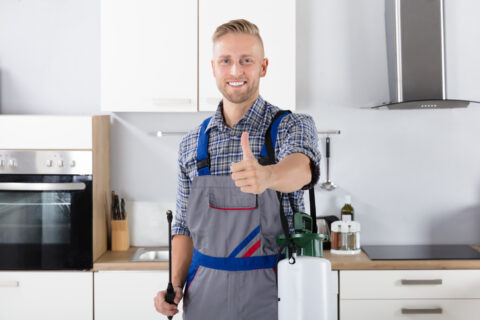 Man standing in kitchen smiling and giving a thumbs up