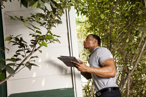 Home inspection on exterior. Man using digital tablet to record results