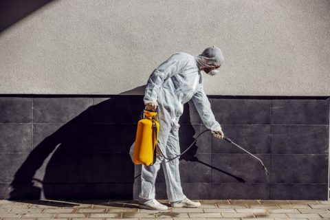Man cleaning around outside of a building